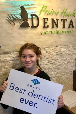 Girl holding up best dentist ever sign